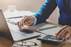 contador-trabajando-oficina-usando-computadora-portatil-calculadora_34152-52